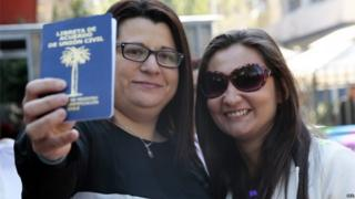 Roxana Ortiz (L) and Virginia Gomez (R) show their civil union agreement card after formalising their union in Santiago (22/10/2015)