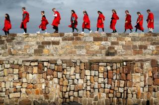 A row of students in red gowns walk along the harbour wall.