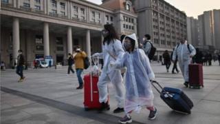 武汉解封后身穿防护服的市民前往车站