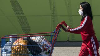 A woman wearing a protective facemask leaves a supermarket in Illzach, eastern France, 16 March 2020