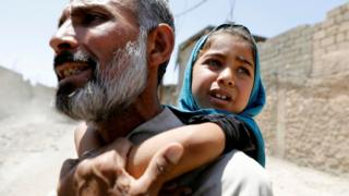 A man displaced by fighting between Iraqi forces and Islamic State militants carries his daughter in Mosul's Zanjili district (7 June 2017)