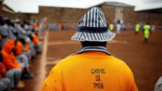 "A Kenyan prisoner wearing a shirt with the words ""Crime is not good"" watches a mock world cup soccer match between Russia and Saudi Arabia, as part of a month-long soccer tournament involving eight prison teams at the Kamiti Maximum Prison, Kenya""s largest prison facility, near Nairobi,"