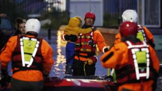 South Yorkshire Fire and Rescue Service carry a child through floods in Doncaster on Friday 8 November