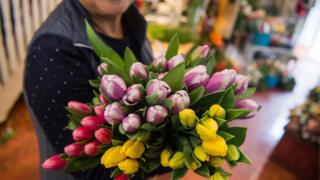 A florist holds tulips in her hands in a flower shop