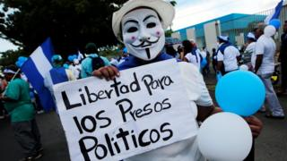 """A masked anti-government protester holds a sign reading """"Freedom for political prisoners"""" in Managua, Nicaragua on 9 September 2018."""