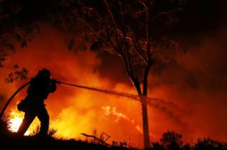 A firefighter is working on extinguishing the Lilac Fire, a fast-moving wildfire in Bonsall, California