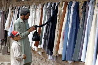 A Pakistani man buys used clothes as he prepares for the upcoming Eid al-Fitr festival, the celebrations marking the end of holy fasting month of Ramadan, in Peshawar, Pakistan, 13 June 2018