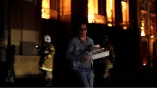 Pesquisadora tenta resgatar objetos de pesquisa do meus em meio a chamas