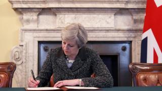 La primer ministro británica, Theresa May, firma la carta anunciando la intención de Reino Unido de abandonar la UE.
