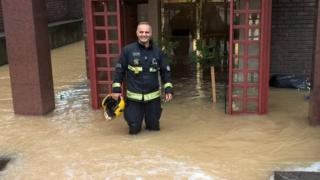 Firefighter standing in floodwater