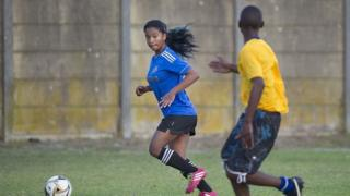Girl is chased by a boy on a football pitch