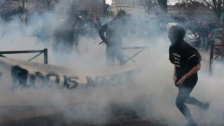 People run away from a smoke grenade launched by riot police forces during a demonstration against police brutality in Paris (23 February 2017)