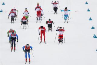 Skiers race on a ski slope in the Mixed Relay Cross-Country Skiing