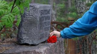 Marina Titova coloca un clavel frente a una lápida en la isla de Mudyug