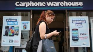 אישה עוברת על פני חנות מחסני Carphone