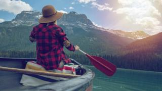 A young woman canoeing on beautiful mountain lake in Canada