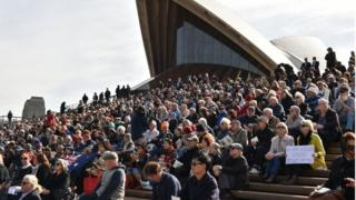 People sits on the steps of the Sydney Opera House to watch the memorial service