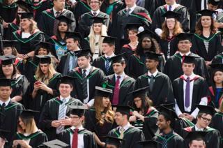 นักศึกษาถ่ายรูปหมู่ในพิธีจบการศึกษา