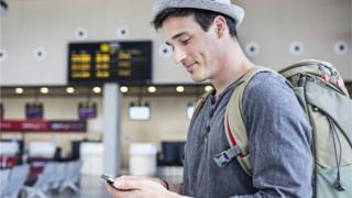 hombre usando teléfono móvil en el aeropuerto.