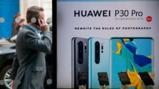 A pedestrian walks past a Huawei product stand