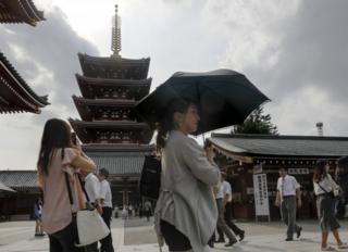 A woman uses her parasol as she walks past the five-storey pagoda at the Sensoji temple in Tokyo