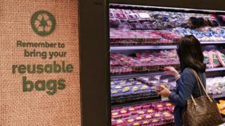 A shopper selects items inside a plastic bag-free Woolworths supermarket in Sydney, Australia, June 15, 2018.
