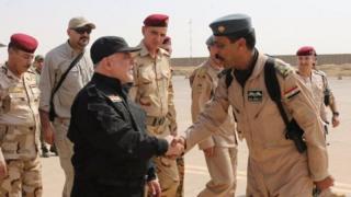 ツイッターで公表されたイラク政府側の戦闘員と握手するアバディ首相の写真
