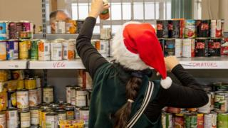 Volunteer stacks food bank shelves