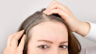 Woman looking at grey hairs appearing