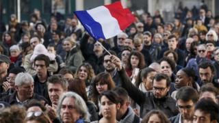 A man waves the French flag at a minute's silence event