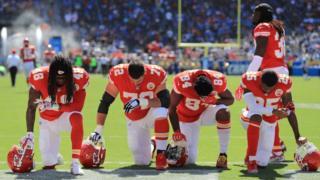 Jugadores de la NFL arrodillados durante el himno estadounidense.