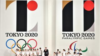 Hammer throw gold medalist Koji Murofushi (C), accompanied by young athletes, delivers a speech as the logo marks of the Tokyo 2020 Olympic (L) and Paralympic (R) Games are unveiled at the Tokyo city hall on July 24, 2015.