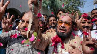 Supporters shower rose petals on Islamic cleric Mufti Abdul Qavi (R), who had been embroiled in controversy with slain social media celebrity Qandeel Baloch