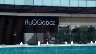 A Kurdish security member stands guard at a restaurant where the attack took place in Irbil