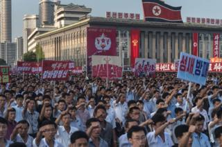 People wave banners and shout slogans as they attend a rally in support of North Korea's stance against the US, on Kim Il-Sung square in Pyongyang