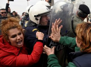 Migrants and refugees, who say that they seek to travel onward to northern Europe, scuffle with police officers near the town of Diavata in northern Greece. 5 April 2019.