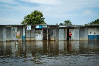 A woman enters a row of kiosks that are flooded.