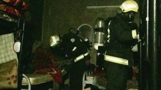 Firefighters examine the inside of the house in Najran