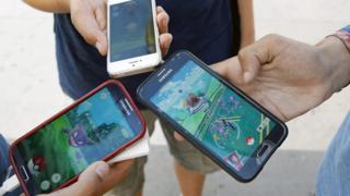 Três pessoas seguram celulares com tela mostrando o game do Pokémon Go