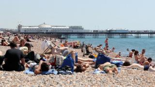 People relax in the sunshine on the beach in Brighton, Sussex