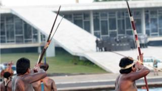 Brazilian indigenous people shoot arrows during a protest at Explanada dos Ministerios in Brasilia, Brazil, on 25 April 2017.