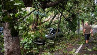A man walks near a car hit by a falling tree following a storm in Timisoara, western Romania. Photo: 17 September 2017