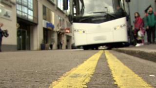 A coach parked on double yellow lines in Belfast