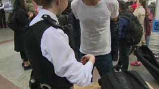 A man being searched by a policewoman