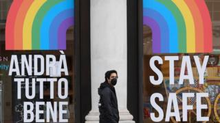 "A man wearing a mask walks past a ""Stay Safe"" message on a shop, following the outbreak of the coronavirus disease (COVID-19), in London, Britain,"