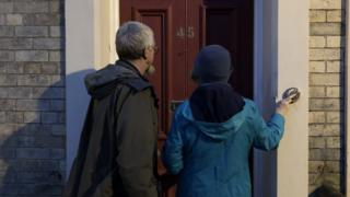 Two people ringing a doorbell