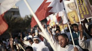 File photo showing Bahrainis shout slogans and wave their national flag during an anti-government protest in Jannusan, west of Manama, on 9 May 2014
