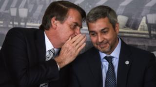 Jair Bolsonaro cobre a boca enquanto fala com Mario Abdo