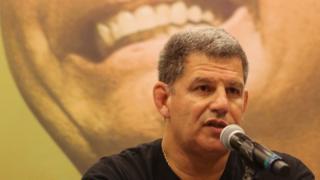 Gustavo Bebianno fala no microfone com foto de Jair Bolsonaro ao fundo