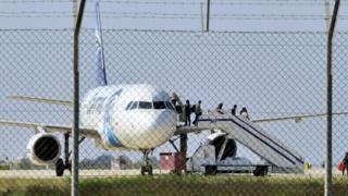 緊急着陸したハイジャック機から降りる乗客たち(29日)